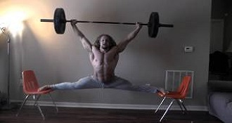 Strong Man Holds Barbell Above His Head While Performing Splits